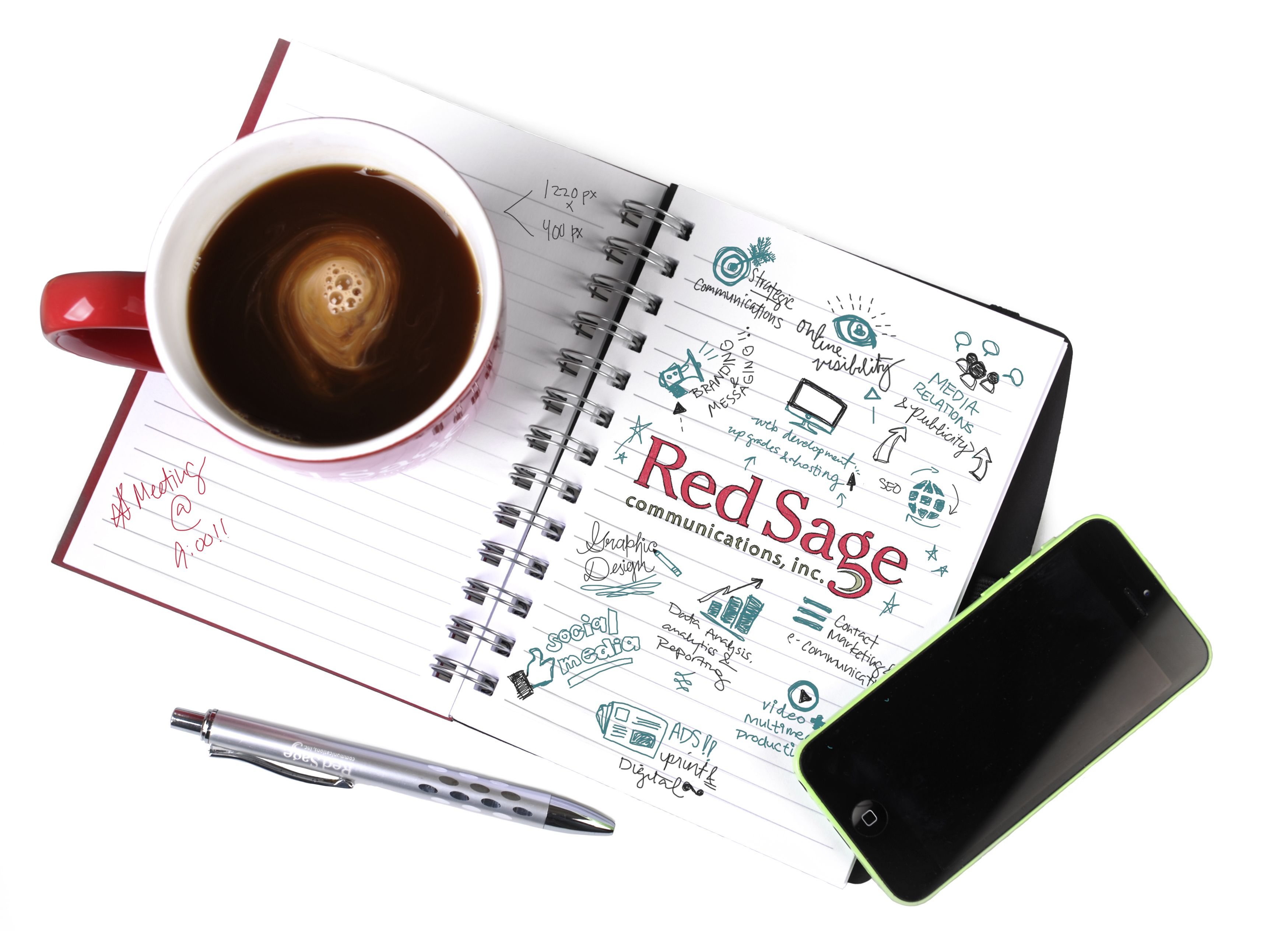 Coffee mug sitting on notebook with Red Sage next to smartphone